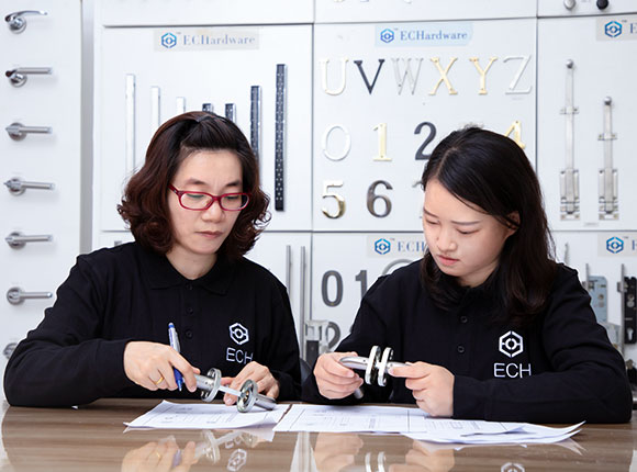 two employees checking door hardware design for odm molding